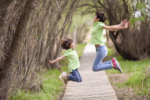 Happy mother and daughter jumping on boardwalk - JSMF00198