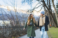 Austria, Innsbruck, happy young couple strolling together hand in hand at winter time - WPEF00227