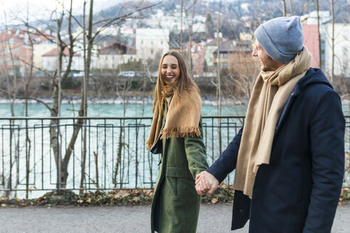 Austria, Innsbruck, happy young couple strolling together hand in hand at winter time - WPEF00230