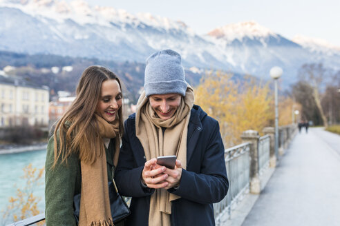 Austria, Innsbruck, happy young couple looking at cell phone - WPEF00233