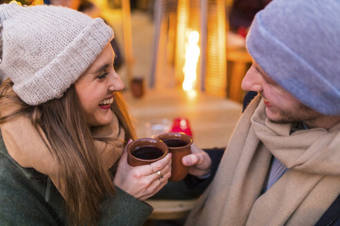 Happy young couple drinking mulled wine at Christmas market - WPEF00242