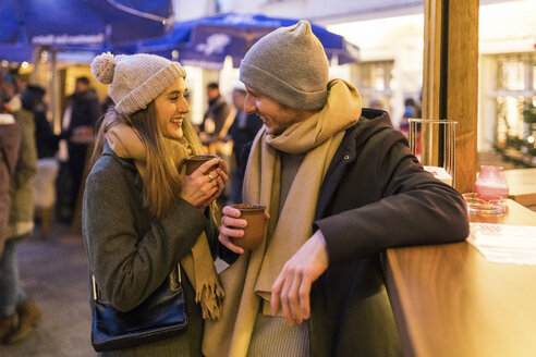 Happy young couple drinking mulled wine at Christmas market - WPEF00245