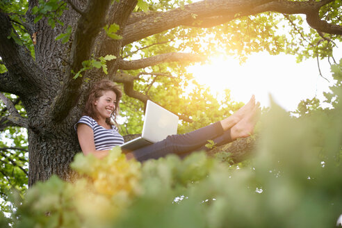 Smiling woman using laptop in tree - CUF00738