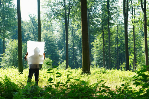 Man in the woods, looking at blueprint - CUF00750