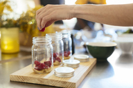 Close-up of woman in kitchen putting raspberry into jar - EBSF02425