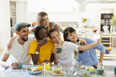 Friends with drinks taking a selfie in kitchen - EBSF02476