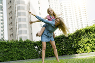 Happy mother and daughter having fun in urban city garden - SBOF01467