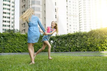 Happy mother and daughter having fun in urban city garden - SBOF01470