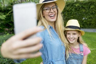 Happy mother and daughter taking a selfie in garden - SBOF01473