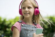 Cute blonde girl listening to music with pink headphones in garden - SBOF01479