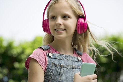 Cute blonde girl listening to music with pink headphones in garden - SBOF01479