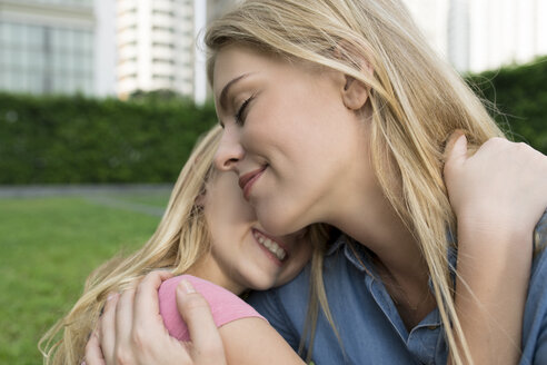 Happy mother and daughter hugging and smiling in urban city garden - SBOF01482