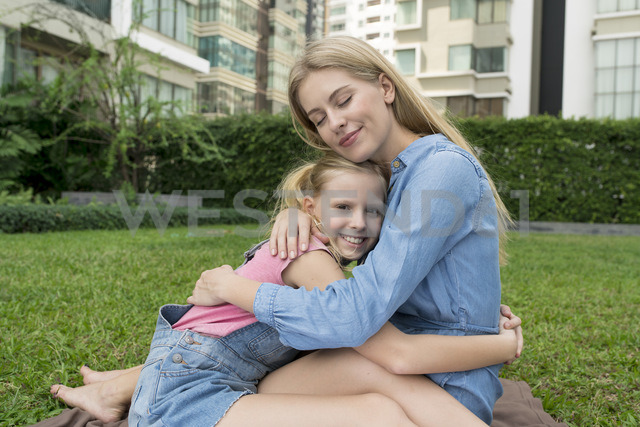 Happy mother and daughter hugging and smiling in urban city garden - SBOF01485