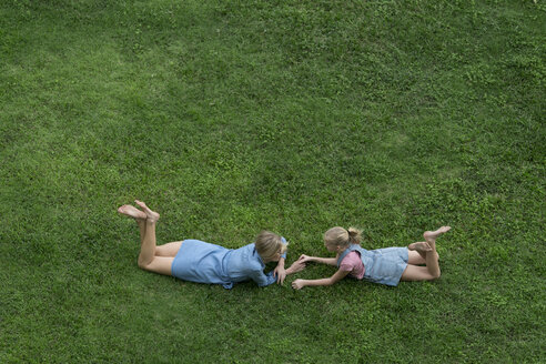 Bird's eye view of mother and daughter talking to each other in garden - SBOF01488