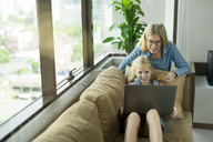 Mother and daughter in modern living room on a couch with laptop and credit card - SBOF01491
