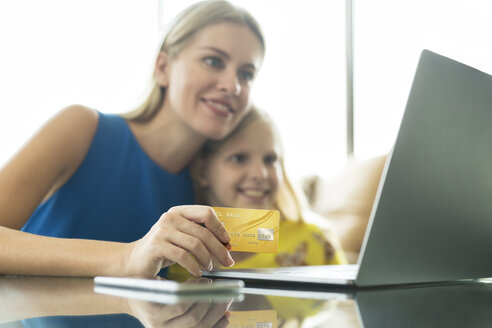 Mother and daughter using laptop and credit card together - SBOF01494