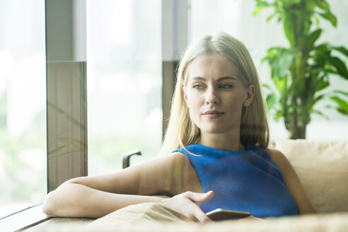 Portrait of attractive woman relaxing on couch at home - SBOF01497