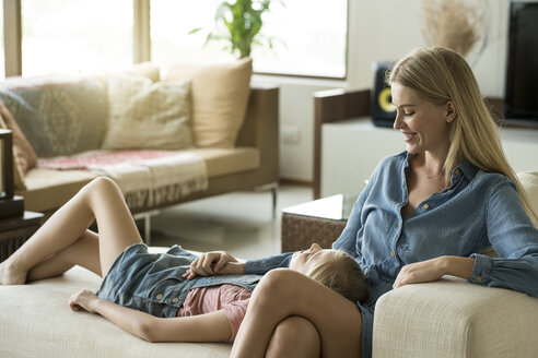 Happy mother and daughter cuddling and relaxing on a couch in a modern living room - SBOF01500