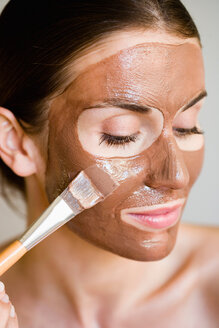 Woman putting face mask on - CUF00783