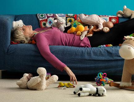 Senior woman asleep on sofa with toys - CUF00831