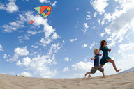 Mother and son flying kite on beach - CUF00885