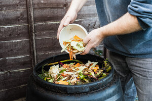 Man adding to compost bin outdoors - CUF00894