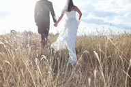 Newlywed couple holding hands in grass - CUF00912