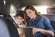 Family on a road trip with mother and son sharing tablet - DIGF04141