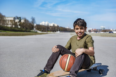 Portrait of smiling boy with longboard and basketball outdoors - DIGF04156