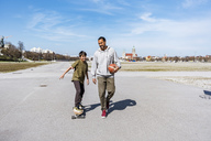 Father and son with longboard and basketball outdoors - DIGF04159