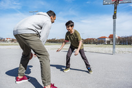 Father and son playing basketball on court outdoors - DIGF04162