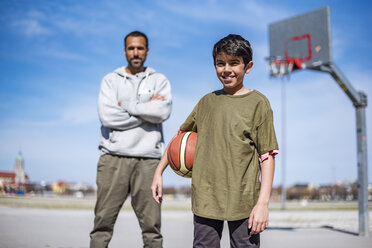 Portrait of boy with father on basketball court outdoors - DIGF04165