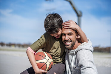 Portrait of happy father and son with basketball outdoors - DIGF04168