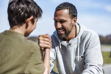 Father and son arm wrestling outdoors - DIGF04177