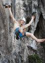 Thailand, Krabi, Lao Liang, barechested climber abseiling from rock wall - ALRF01160