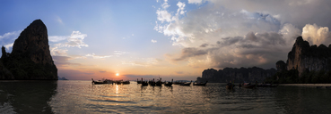 Thailand, Krabi, Railay beach, bay with long-tail boats floating on water at sunset - ALRF01175