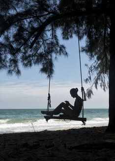 Thailand, Krabi, Lao liang island, woman on tree swing on the beach - ALRF01187