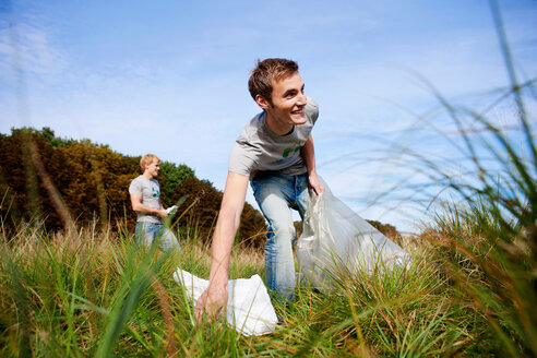 Young man collecting trash in nature - CUF00962