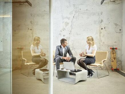 Businessman and businesswoman talking in modern office - CVF00348