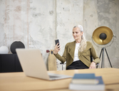 Businesswoman looking at cell phone in office - CVF00357