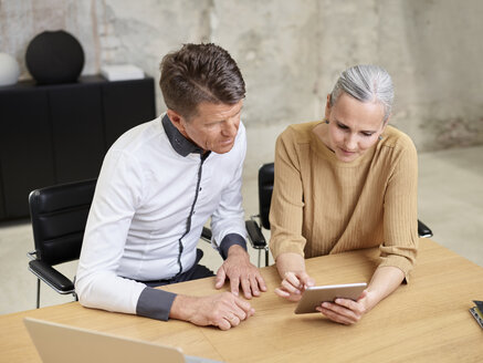 Businessman and businesswoman sharing tablet in office - CVF00360