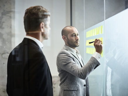 Businessman looking at colleague writing on sticky notes at glass pane in office - CVF00372