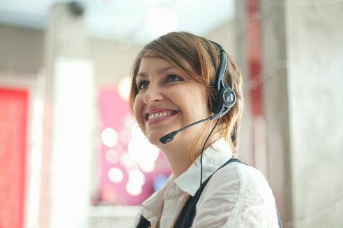 Businesswoman wearing headset at desk - CUF01108