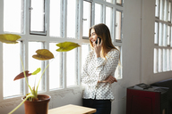 Happy young woman on cell phone at the window in office - EBSF02493