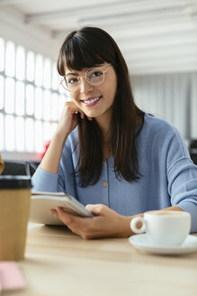 Portrait of smiling young woman with notepad at desk in office - EBSF02502