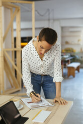 Woman working on draft at desk in office - EBSF02520
