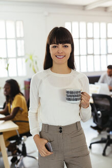 Portrait of smiling young woman in office with colleagues in background - EBSF02526