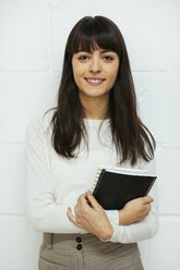 Portrait of smiling young woman with notebook at brick wall - EBSF02559