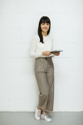 Portrait of smiling young woman with notebook standing at brick wall - EBSF02562