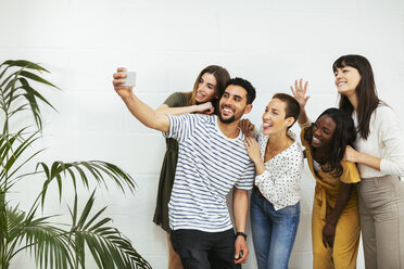 Playful colleagues standing at brick wall taking a selfie - EBSF02565